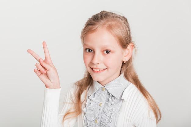 Meisje dat overwinningsteken toont Gratis Foto