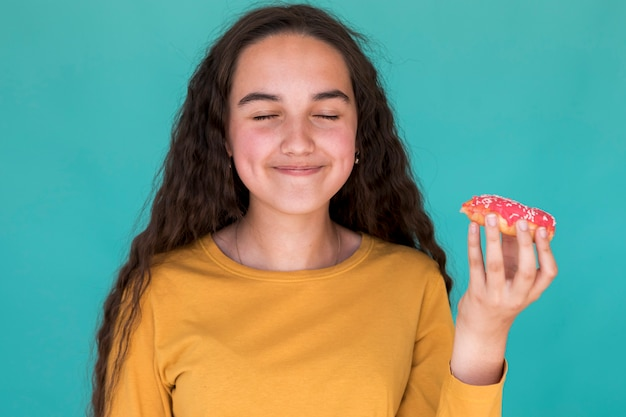 Meisje dat van een verglaasde doughnut geniet Gratis Foto
