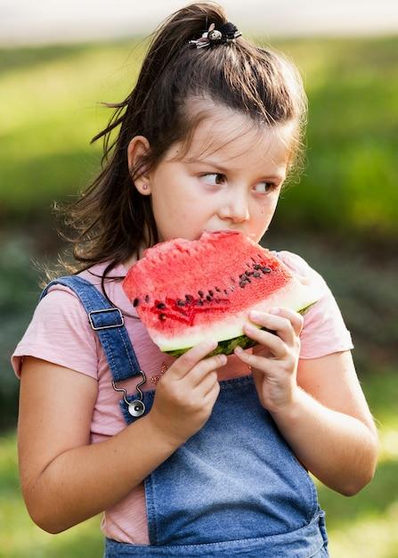 Meisje dat van plak van watermeloen geniet Gratis Foto