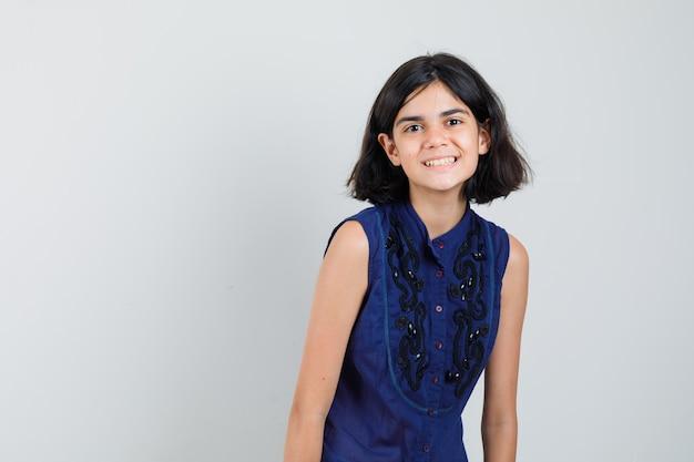 Meisje dat voorzijde in blauwe blouse bekijkt en gelukkig kijkt. Gratis Foto