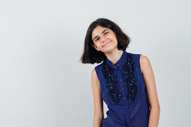 Meisje dat voorzijde in blauwe blouse bekijkt en mooi kijkt. Gratis Foto