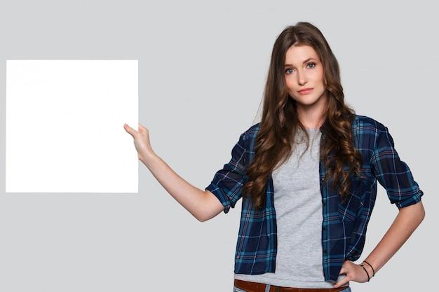 Meisje dat wit aanplakbord houdt Gratis Foto
