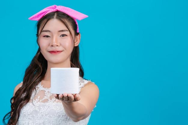 Meisje dat witte pyjama draagt die een papieren zakdoekje in de hand op het blauw houdt. Gratis Foto