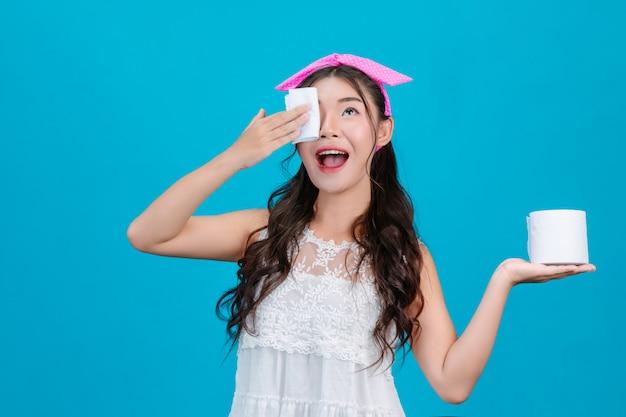Meisje dat witte pyjama draagt die papieren zakdoekje op haar gezicht op een blauw gebruiken. Gratis Foto
