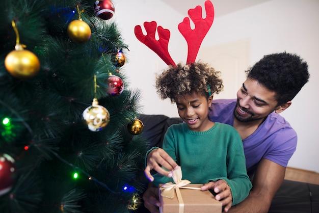 Meisje dat zich bij de kerstboom in de omhelzing van haar vader bevindt en de huidige doos uitpakt Gratis Foto