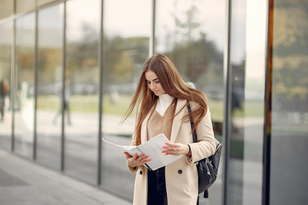 Meisje dat zich in een de lentestad bevindt en documenten in haar hand houdt Gratis Foto