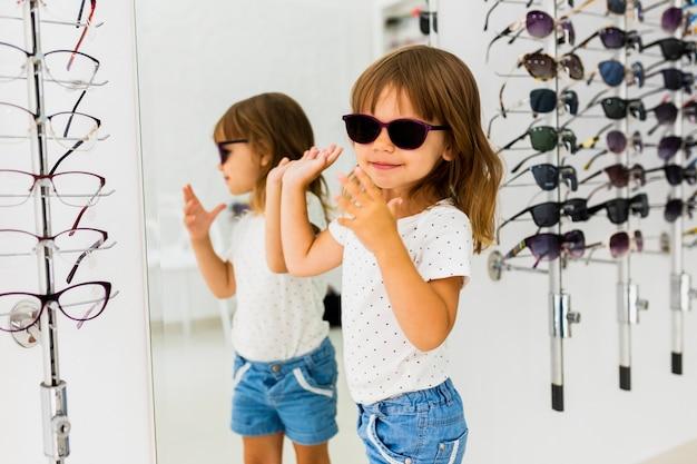Meisje dat zonnebril in winkel draagt Gratis Foto