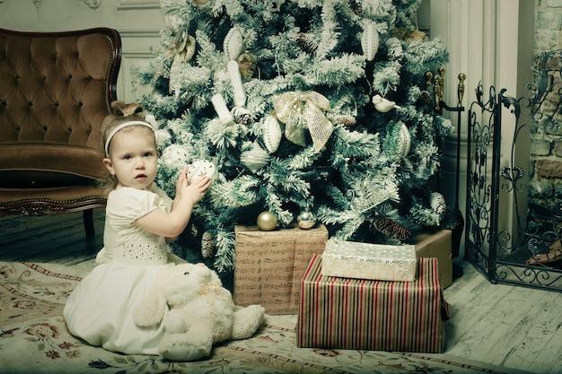 Meisje dichtbij cristmassboom Premium Foto