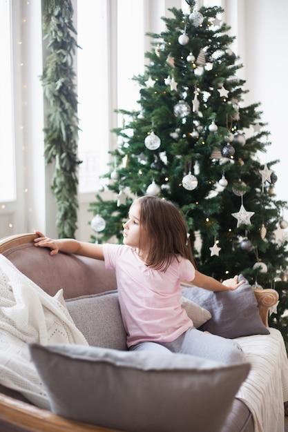 Meisje dichtbij hij kerstboom, wachtend op de kerstman en een wonder Premium Foto