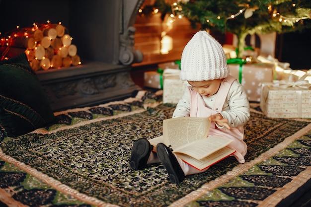Meisje die dichtbij kerstmisboom zitten Gratis Foto
