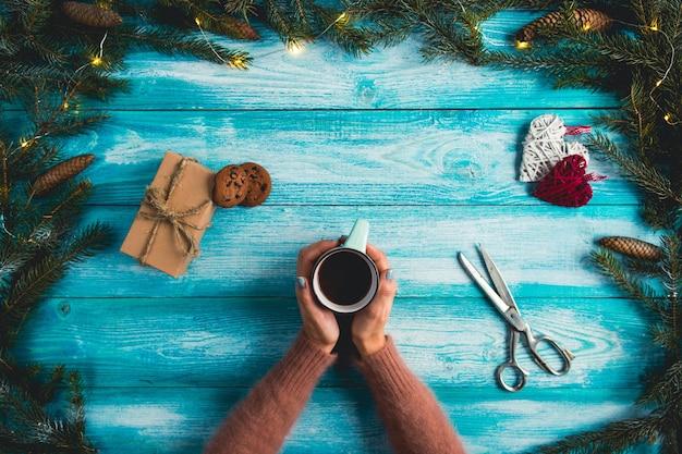 Meisje die een kop van hete cacao op een houten blauwe achtergrond houden. kerst concept. Gratis Foto