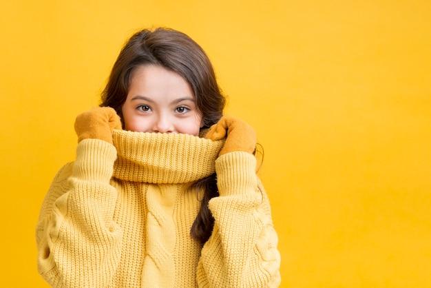 Meisje die haar mond behandelen met haar sweater Gratis Foto