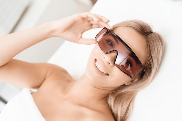 Meisje die in glazen in witte afdeling op de verwijdering van het laserhaar wachten Premium Foto