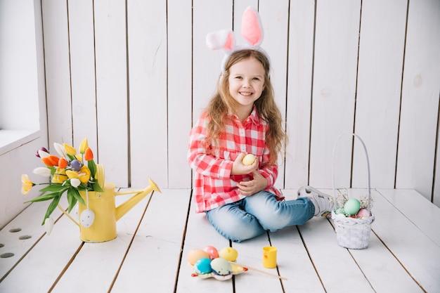 Meisje die in konijntjesoren op vloer met gekleurde eieren zitten Gratis Foto
