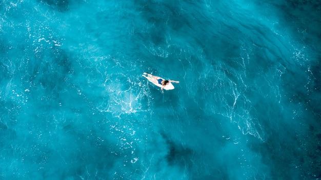Meisje die op een surfplank leggen en in de open zee met glashelder water in de maldiven drijven Gratis Foto