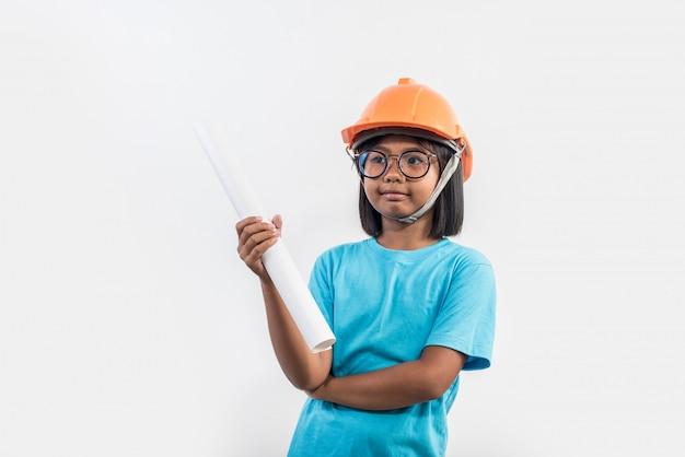 Meisje die oranje helm in studioschot dragen Gratis Foto