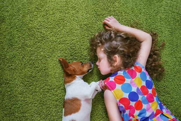 Meisje die puppyhefboom russell omhelzen en op groen tapijt liggen. hoge bovenaanzicht. Premium Foto