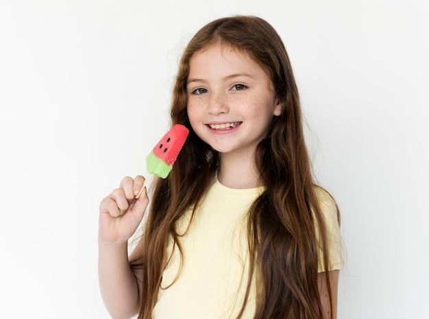 Meisje die roomijsdessert eten die op witte achtergrond glimlachen Premium Foto