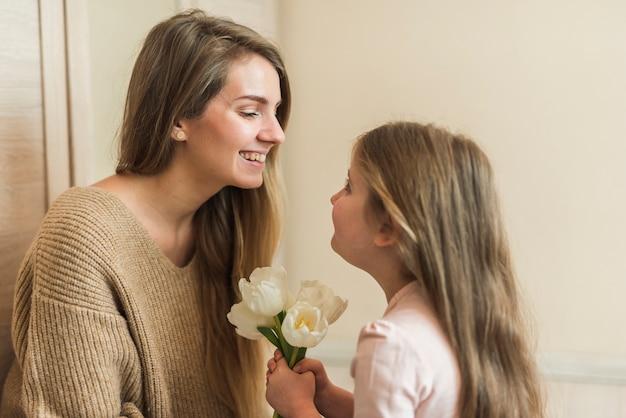 Meisje die tulpenbloemen geven aan moeder Gratis Foto