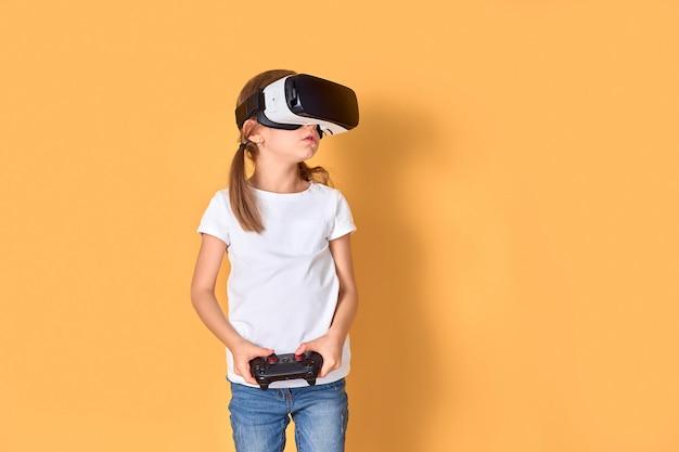 Meisje die vr-hoofdtelefoon versus joystickspel ervaren. verraste emoties op haar gezicht. kind gebruikt een gaminggadget voor virtual reality. Premium Foto