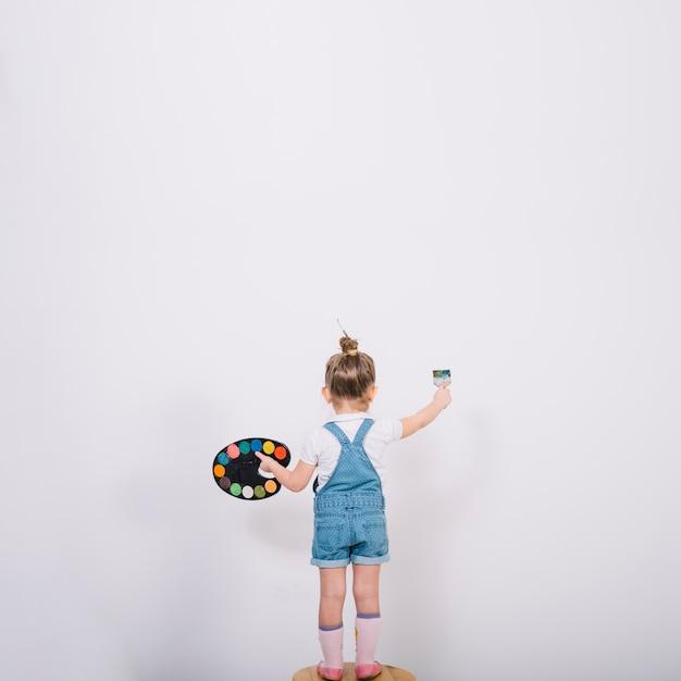 Meisje die zich op stoel en muur met borstel bevinden schilderen Gratis Foto