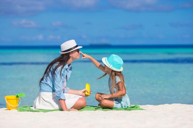 Meisje die zonroom toepassen op haar moederneus Premium Foto