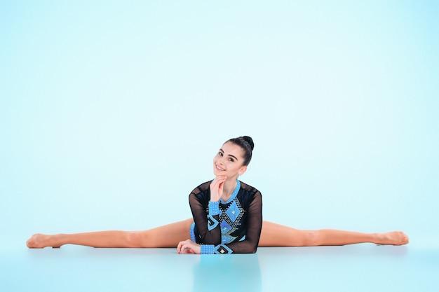 Meisje doet gymnastiek dans op blauw Gratis Foto