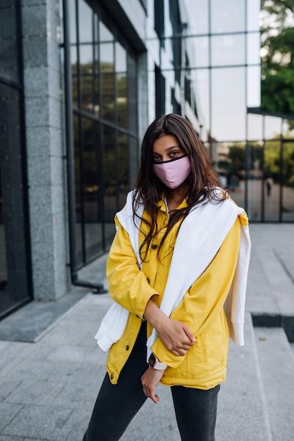 Meisje draagt masker poseren op straat. mode tijdens quarantaine van uitbraak van coronavirus. Gratis Foto