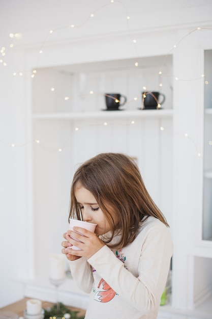 Meisje drinken uit een glas sap of drankje, slingers en staat, de kamer is ingericht voor kerstmis Premium Foto