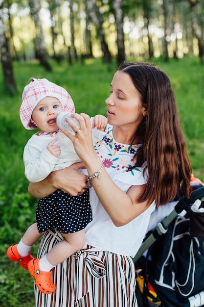 Meisje drinkt water uit een babyfles Premium Foto