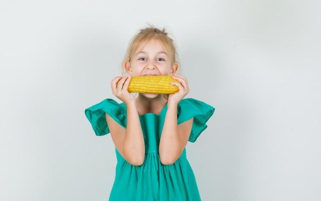 Meisje eet maïs in groene jurk en ziet er vrolijk uit Gratis Foto