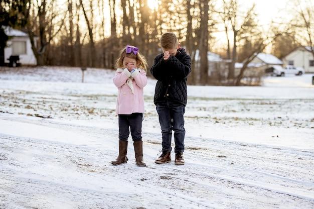 Meisje en een jongen staan en bidden tijdens de zonsondergang Gratis Foto