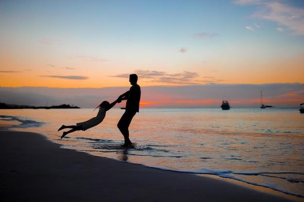 Meisje en gelukkig vadersilhouet in de zonsondergang bij het strand Premium Foto