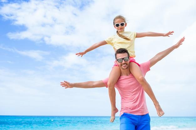 Meisje en gelukkige papa die pret hebben tijdens strandvakantie Premium Foto