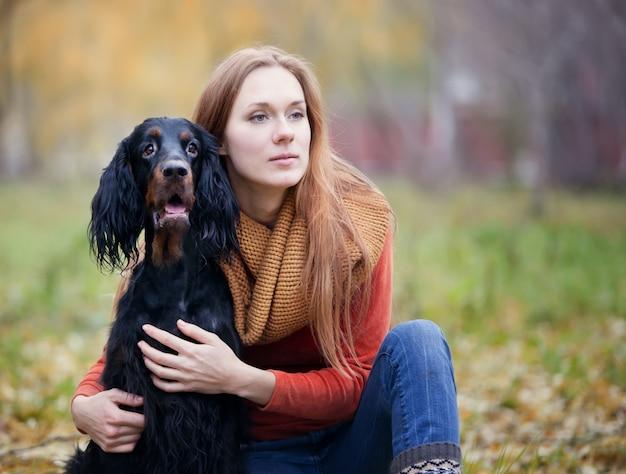 Meisje en haar hond gordon zetter in het de herfstpark Premium Foto
