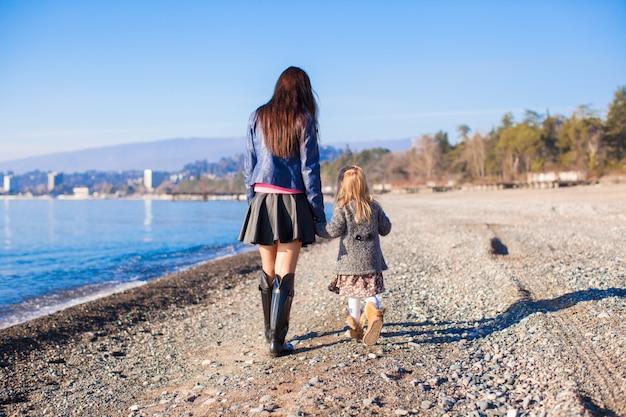 Meisje en haar moeder die op het strand in de winter zonnige dag lopen Premium Foto