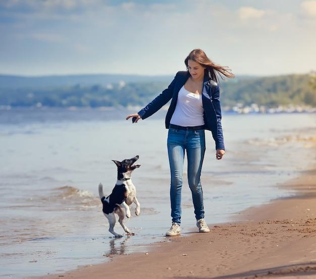 Meisje en hond die op een strand lopen Premium Foto