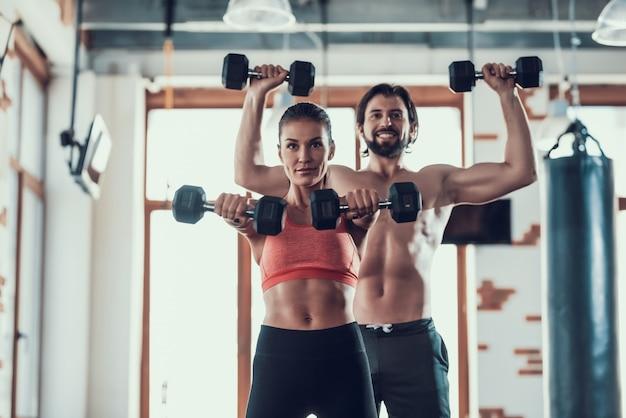 Meisje en man in de sportschool doen halters oefeningen. Premium Foto