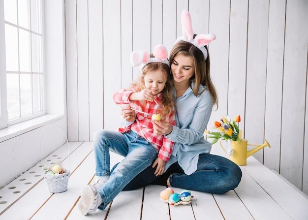 Meisje en moeder in konijntjesoren die eieren voor pasen schilderen Gratis Foto