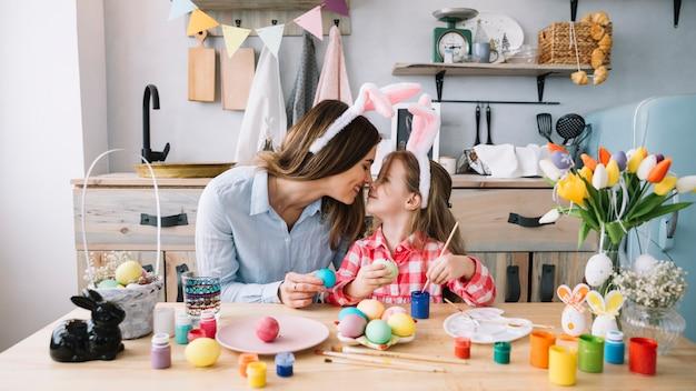 Meisje en moeder wat betreft neuzen terwijl het schilderen van eieren voor pasen Gratis Foto