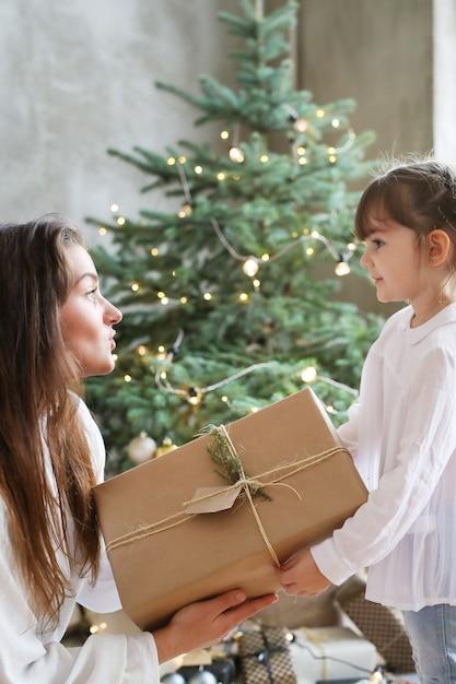 Meisje en vrouw met kerstboom en aanwezig Gratis Foto