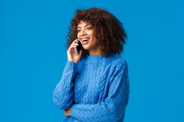 Meisje feliciteert familie met fijne feestdagen, wenst goed nieuwjaar als praten over de telefoon vanuit het buitenland, houdt smartphone aan het spreken, belt vriend, kijkt naar links en lacht, blauwe muur Premium Foto