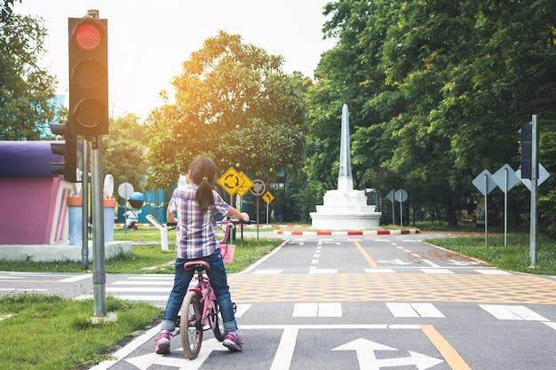 Meisje fietst in het park, fiets stopt bij verkeerslichten Premium Foto