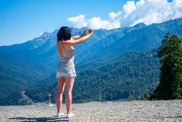 Meisje fotografeert het berglandschap op de smartphone Premium Foto