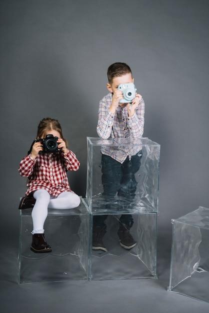 Meisje fotograferen met camera en jongen fotograferen met vintage instant camera Gratis Foto