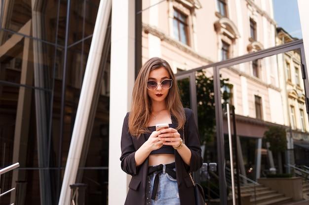Meisje gebruikt een smartphone op een stadsstraat Premium Foto