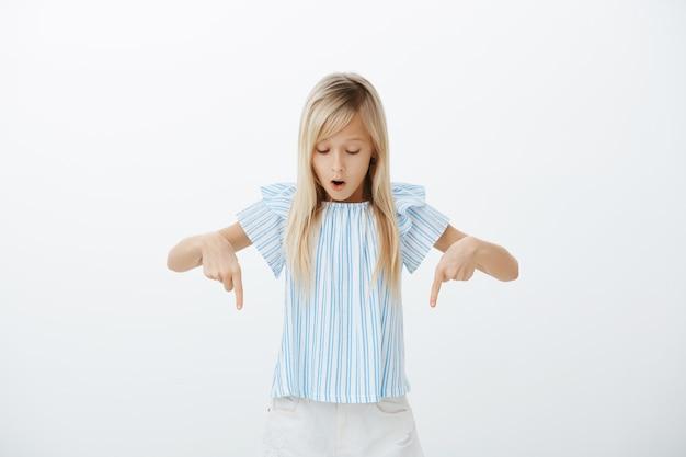 Meisje gefascineerd en opgewonden tijdens het lopen op de glazen vloer. portret van verbaasd aantrekkelijke blonde jonge dochter in schattige blauwe blouse wijzend en neerkijkt met opengevallen kaak, staande over grijze muur Gratis Foto