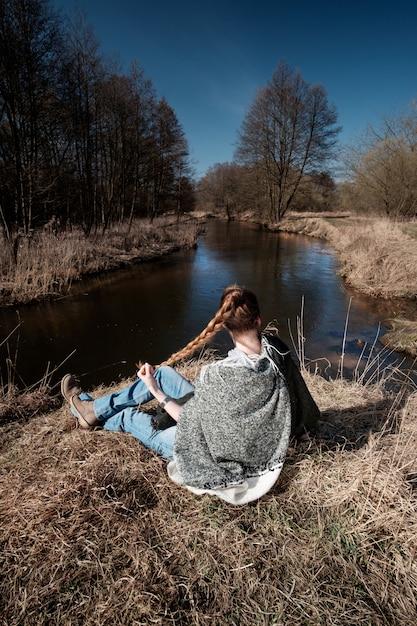 Meisje gekleed in jeans en grijze hoody zittend op de oever van de rivier Premium Foto