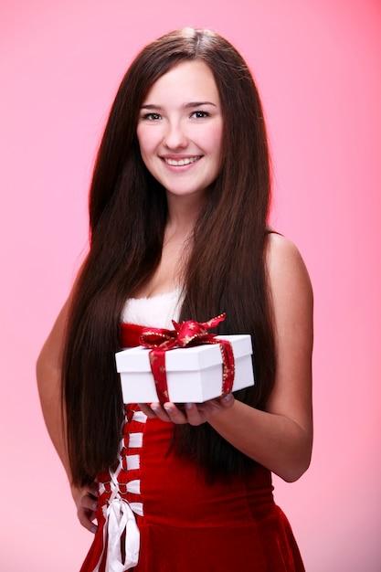 Meisje glimlachend met een kerstcadeau Gratis Foto