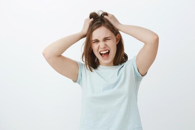 Meisje haat te veel nadenken. ontevreden, verontruste jonge, boos europese vrouw met bruin kort kapsel, gillend terwijl ze boos wordt, boos of gek is, haar verprutst of haar uit het hoofd trekt Gratis Foto